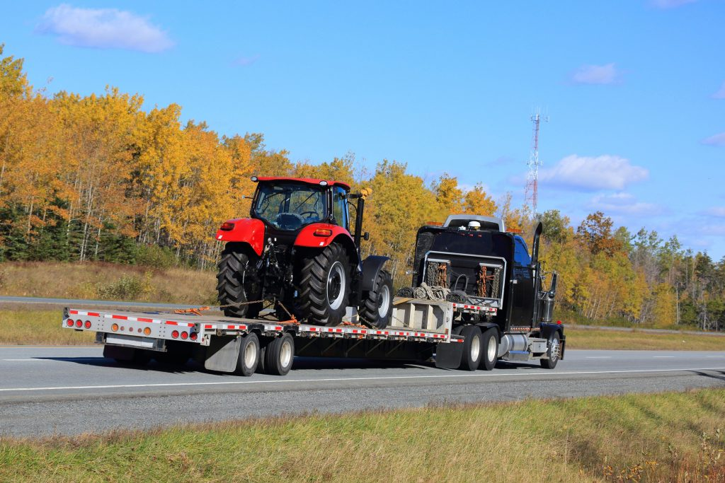 New tractor on a flatbed trailer, being delivered by a semi truck.