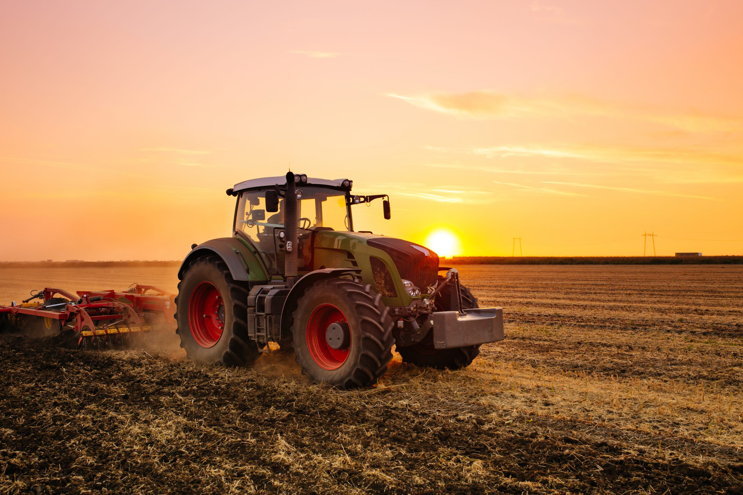 Tractor tilling a field at sunset